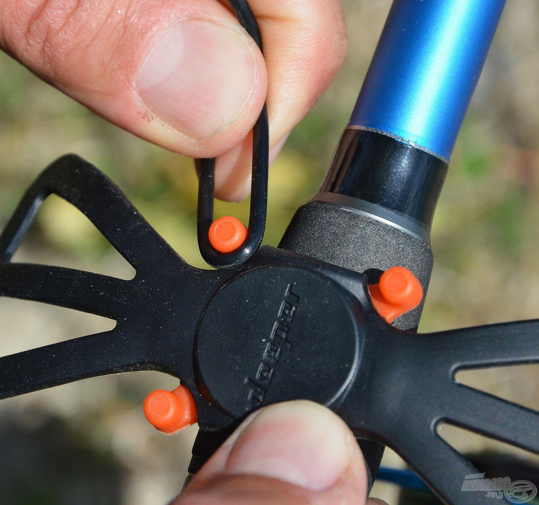 … majd az egyik szilikon karikát beakasztani a négy narancssárga tartóelem egyikéhez