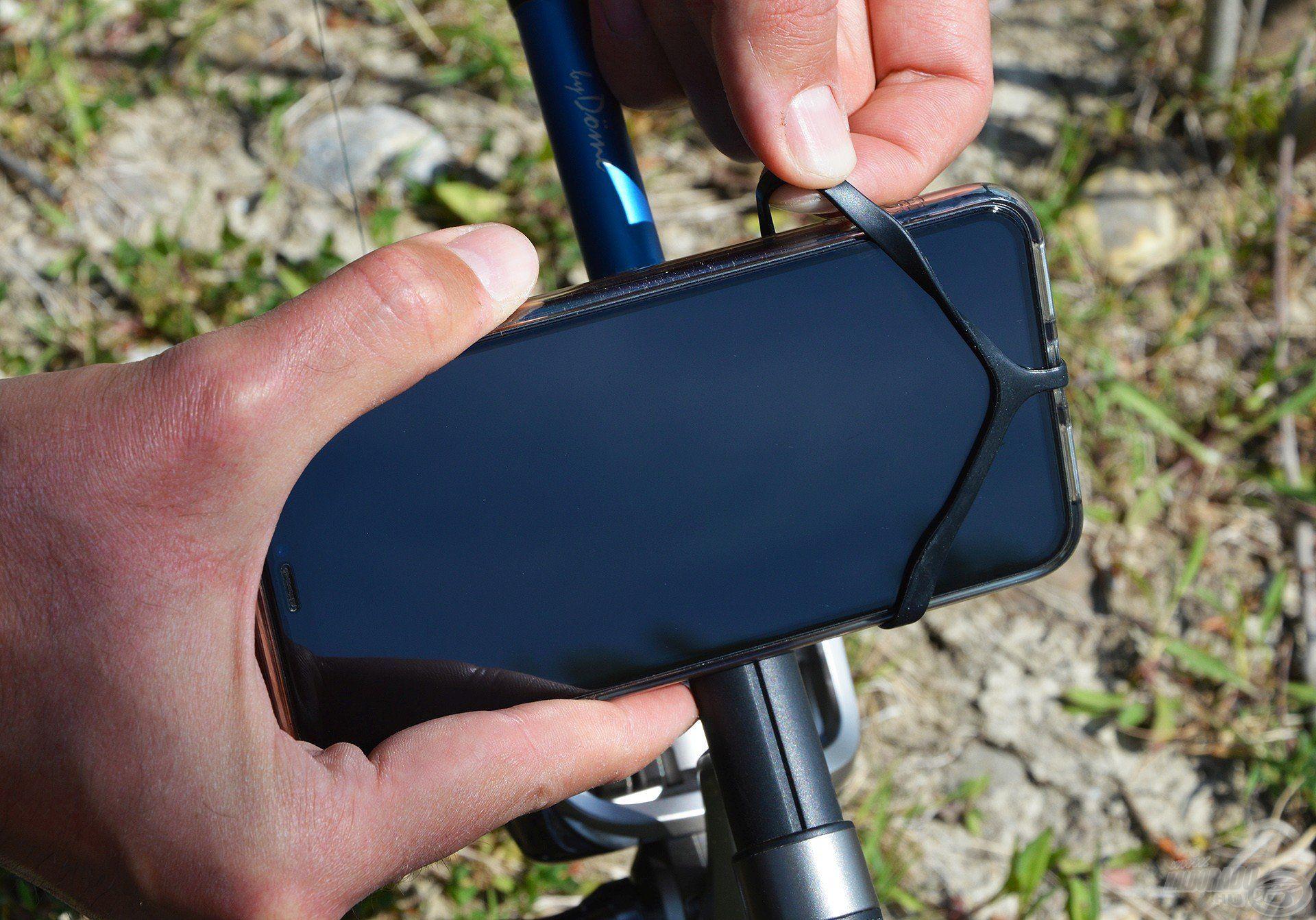 Mehet bele a telefon, amit két oldalon, a négy sarkánál kell a gumik közé illeszteni!