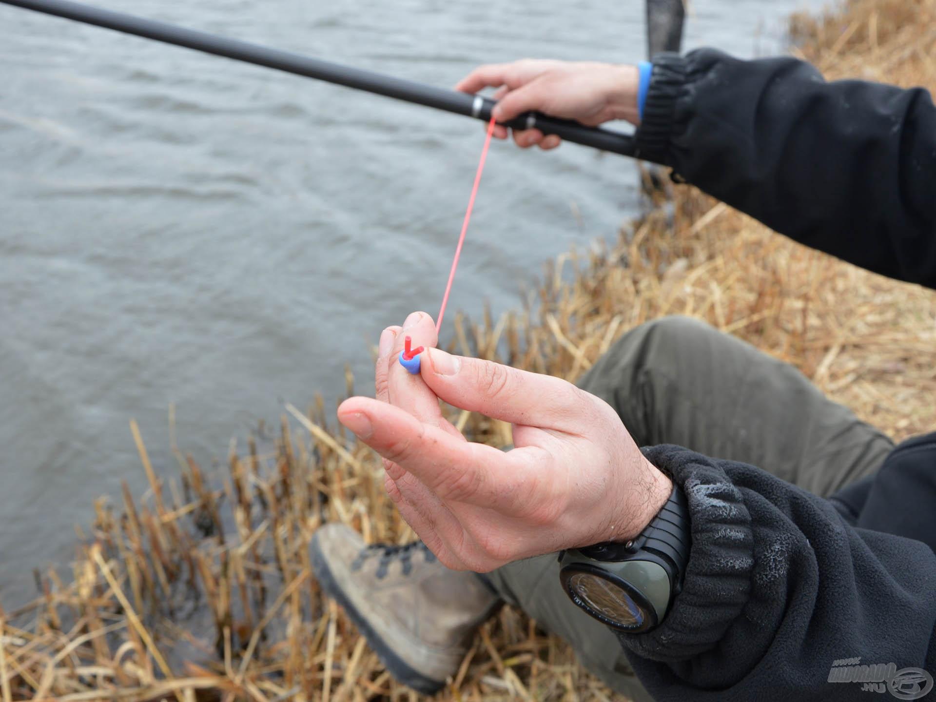 Egyik kezünkkel feszítjük a gumit, míg a másikkal fogjuk a top szettet és egyik ujjunkkal lefogjuk a gumit, nehogy vissza tudja a hal húzni